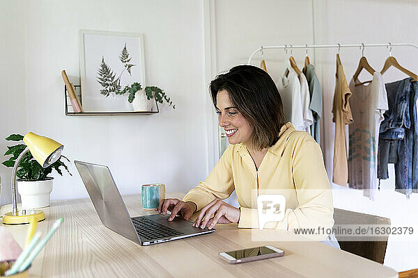 Happy beautiful woman surfing net through laptop at home