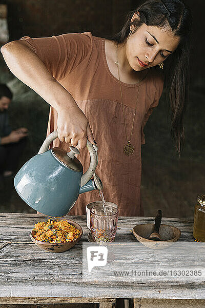 Beautiful woman pouring hot water in glass while preparing herbal tea on wooden table