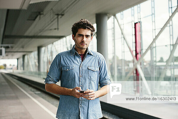 Confident casual businessman using smart phone while standing ta railroad station platform