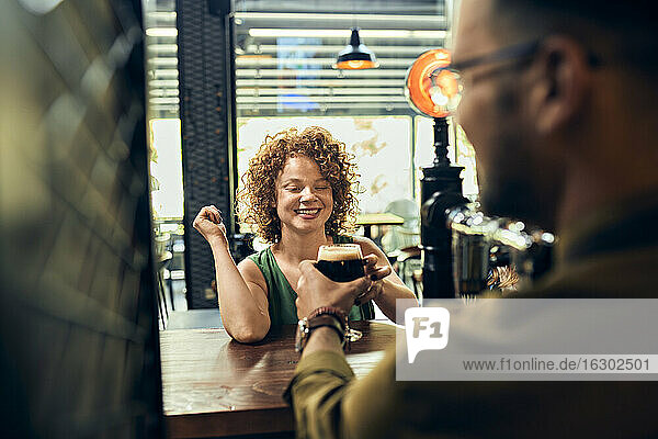 Barkeeper handing over glass of beer to woman in a pub