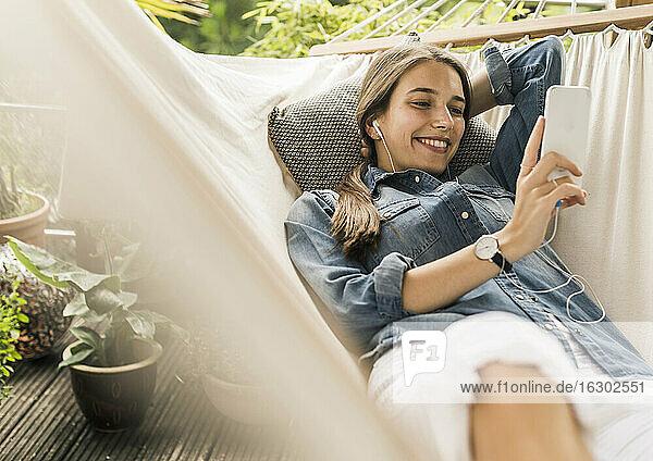 Smiling woman wearing denim jacket using smart phone while lying on hammock in yard