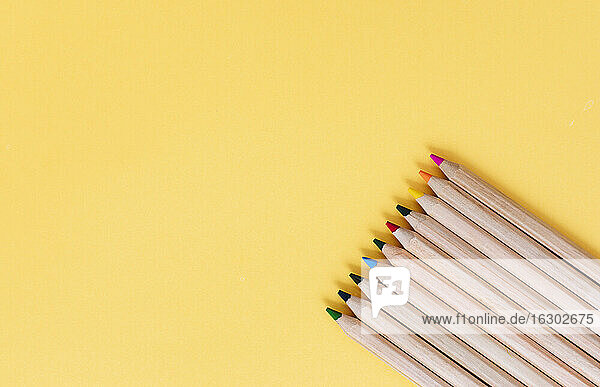 Colored pencils arranged on yellow background
