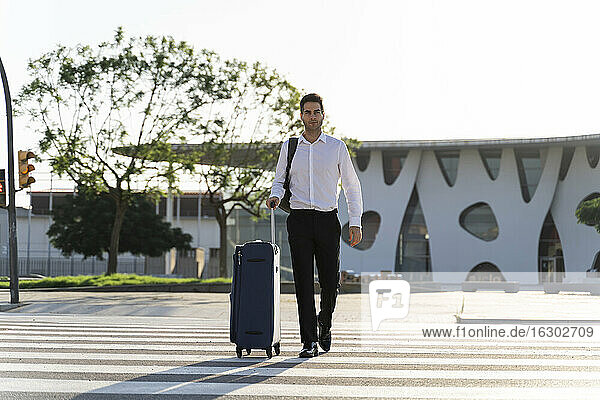 Businessman with suitcase crossing road against clear sky during sunny day