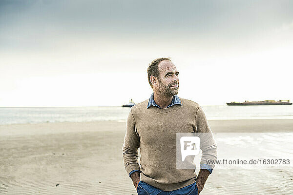 Mature man with hands in pockets contemplating while standing at beach during weekend