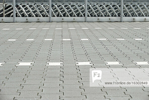 Pavement of a parking place with shopping carts in the background