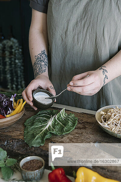 Young woman preparing vegan roll with yoghurt sauce