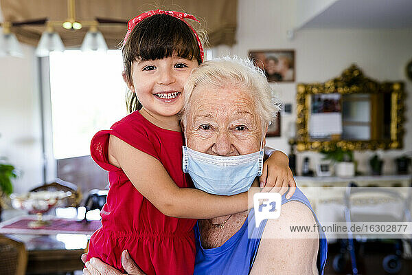Grandmother and little girl spending family time together at home  with face mask