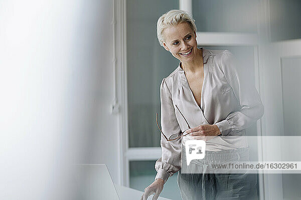 Smiling businesswoman looking away while using laptop against wall in office