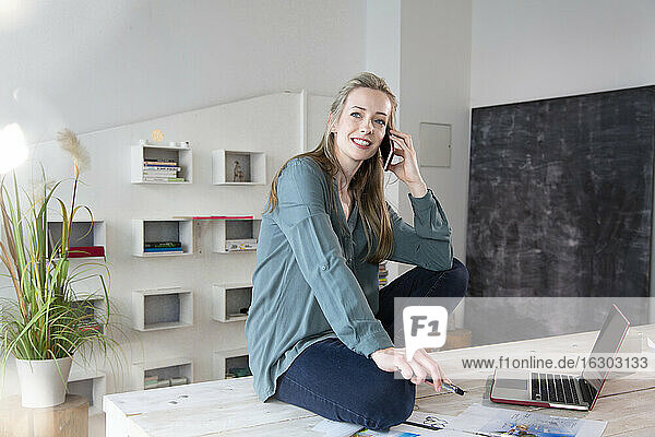 Woman sitting on desk in home office talking on the phone