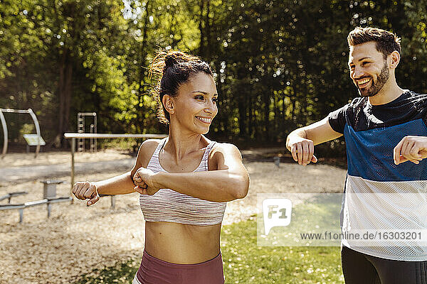 Man and woman stretching near a fitness trail