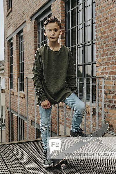 Boy skateboarding on boardwalk against building