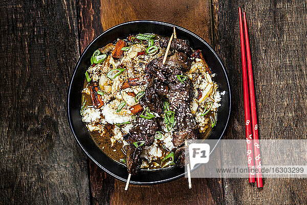 Bowl ofready-to-eatteriyakirice with Chinese cabbage and grilled beef skewers