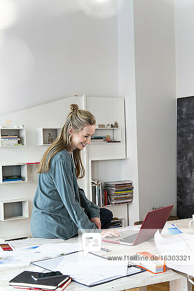 Smiling woman using laptop on desk in home office
