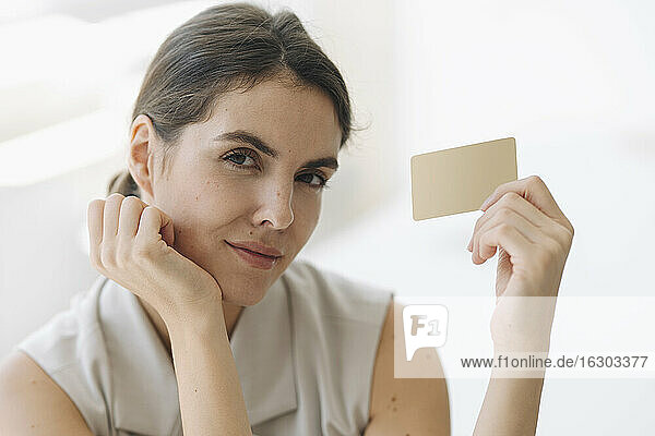 Confident businesswoman holding business card at office