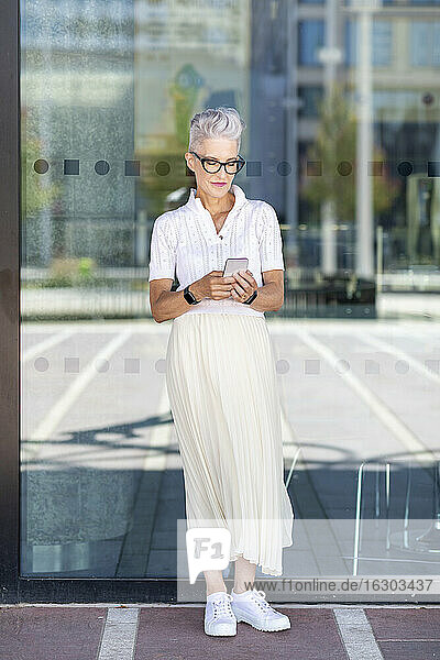 Senior woman using smart phone while standing against glass window on footpath