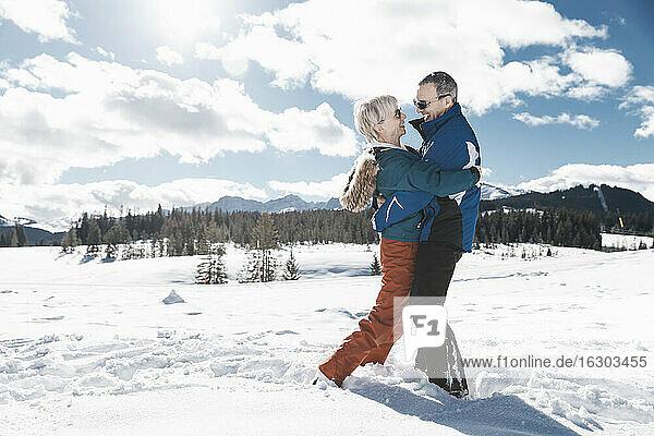 Germany  Bavaria  Winklmoosalm  Mature couple hugging in snow
