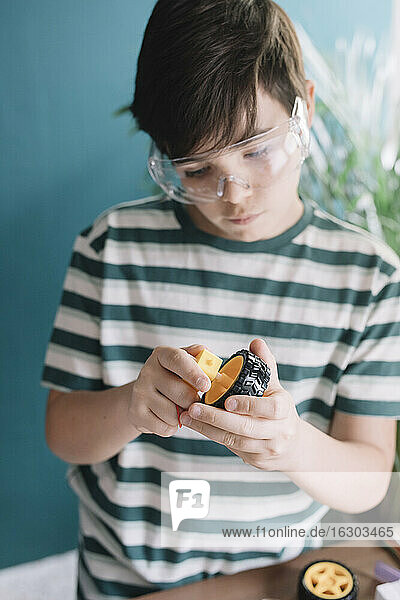 Close-up of boy making robotic toy at home