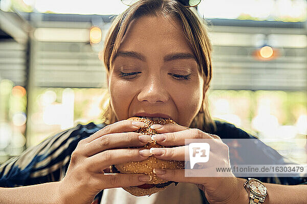 Portrait of woman eating a burger