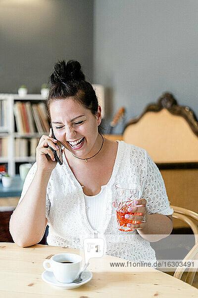 Fröhliche junge Frau  die ein Getränk in der Hand hält und über ein Smartphone spricht  während sie in einem Café sitzt