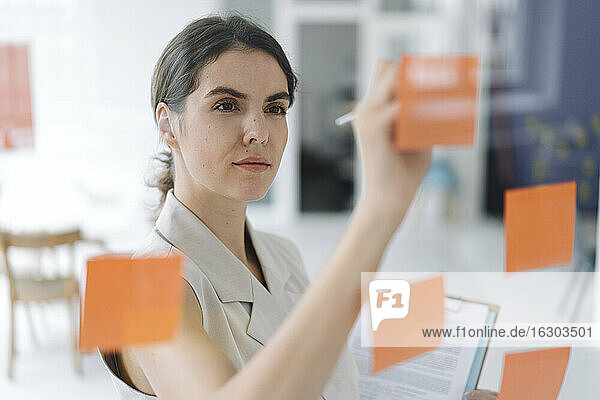Woman writing on sticky note while standing at office