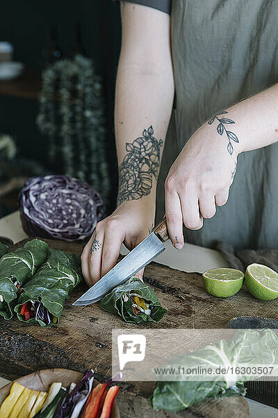 Young woman cutting vegan roll with vegetableson cutting board