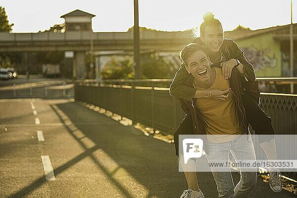 Verspielter Freund nimmt seine Freundin an einem sonnigen Tag in der Stadt huckepack Verspielter Freund nimmt seine Freundin an einem sonnigen Tag in der Stadt huckepack