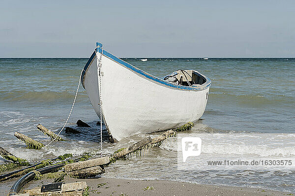 Boat moored at sandy coastal beach