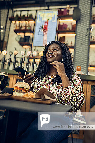 Smiling woman having a burger in a pub