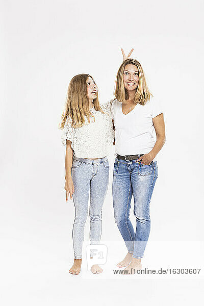 Cheerful girl doing rabbit ears gesture behind mother's head while standing against white background