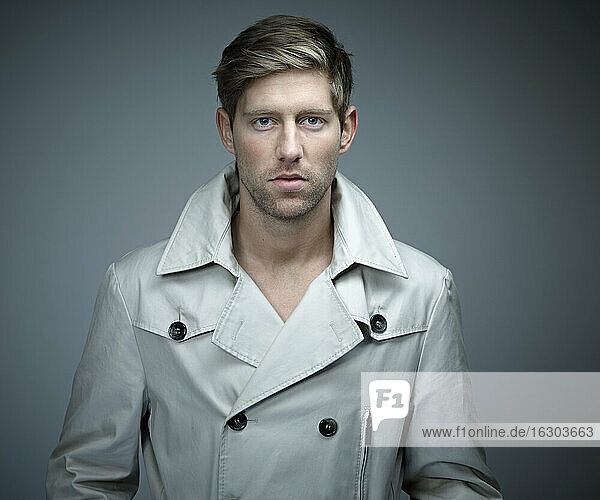 Portrait of young man wearing trench coat