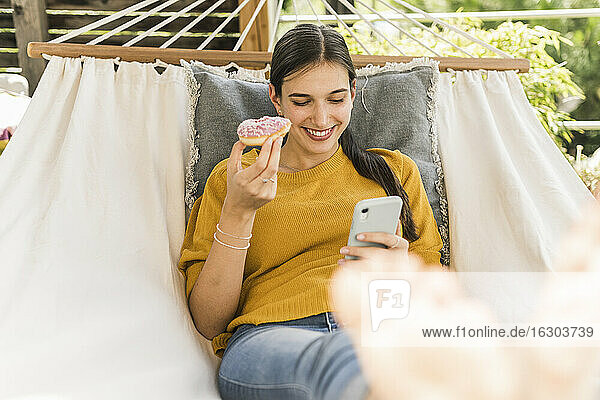 Smiling beautiful woman holding donut while using mobile phone on hammock in yard