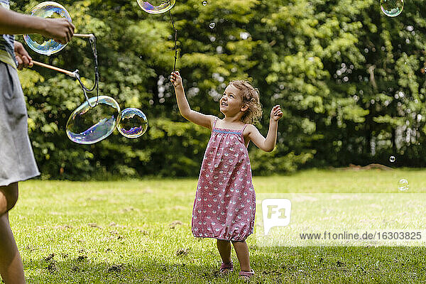 Cute girl exploding bubble with stick by brother at park