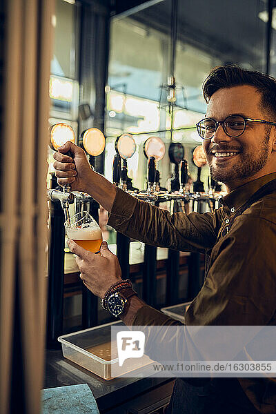 Portrait of smiling barkeeper tapping beer in a pub