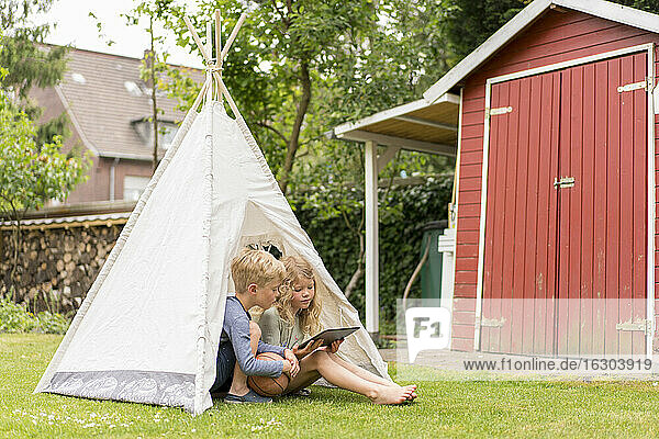 Blond kids with digital tablet sitting in tent on grass at back yard during weekend