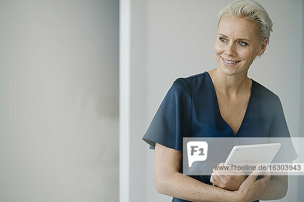 Smiling female entrepreneur with digital tablet looking away while standing against wall in office