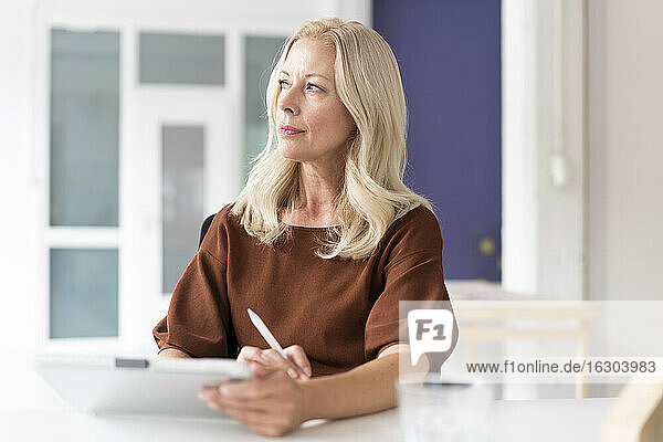 Thoughtful female professional with digital tablet on desk sitting at home