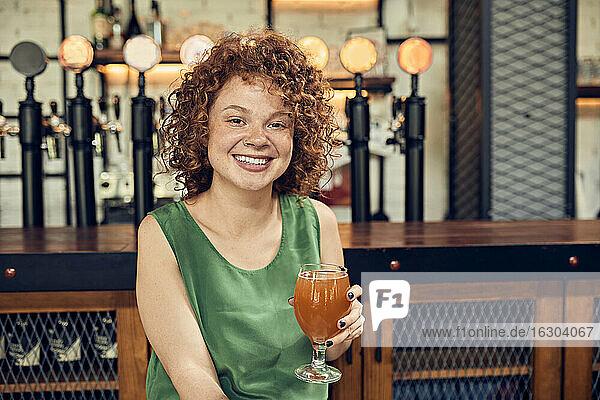 Porträt einer lächelnden Frau in einer Kneipe  die ein Bier trinkt Porträt einer lächelnden Frau in einer Kneipe, die ein Bier trinkt