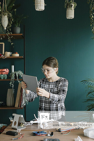 Girl using digital tablet while making quadcopter on table at home