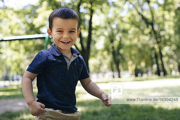 Smiling cute boy playing in ground during summer
