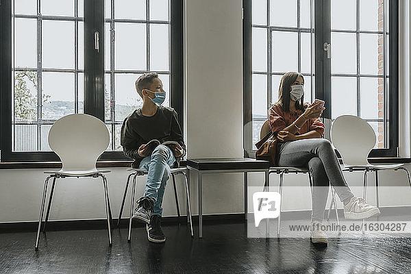 Teenager-Mädchen und Junge mit Masken  die auf Stühlen im Wartezimmer sitzen