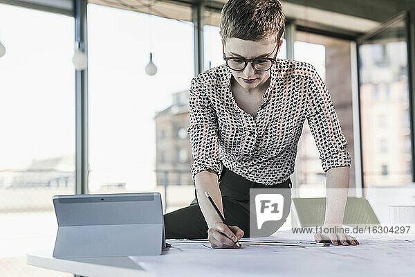 Businesswoman working on plan in office