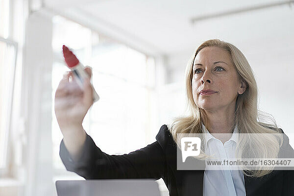 Female entrepreneur writing on window with felt tip pen in home office seen through glass