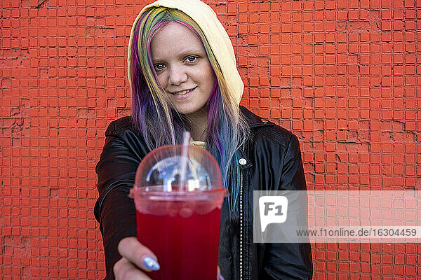 Portrait of young woman with dyed hair with takeaway drink in front of red wall