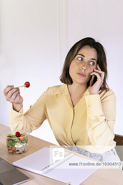 Beautiful young female professional eating salad while talking on mobile phone at home