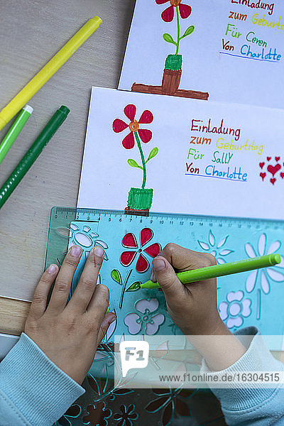 Cropped image of girl hands drawing flowers on papers at table