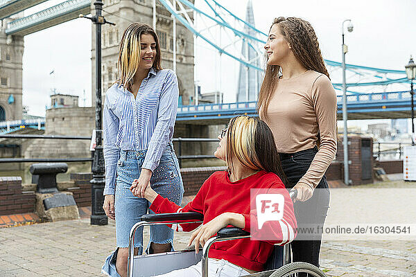 Young women spending leisure time with disabled female friend in city during weekend  London  UK