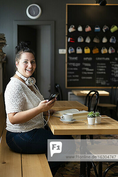 Cheerful young woman using smart phone while sitting at table in coffee shop