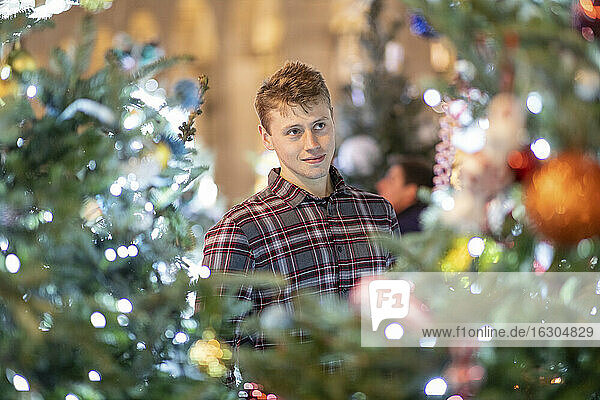 Young man looking at illuminated Christmas tree and lights in city