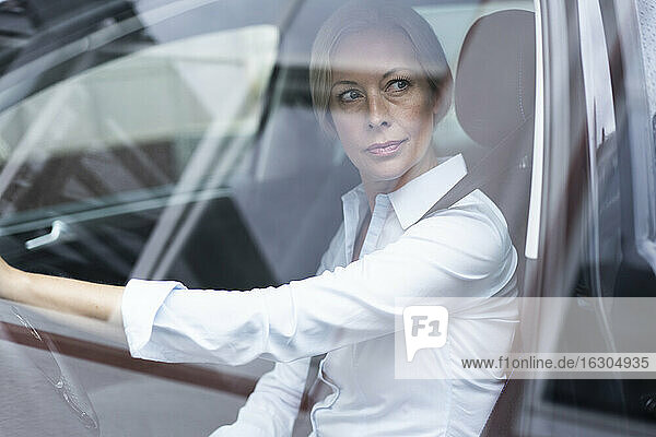 Businesswoman looking away while driving car seen through window