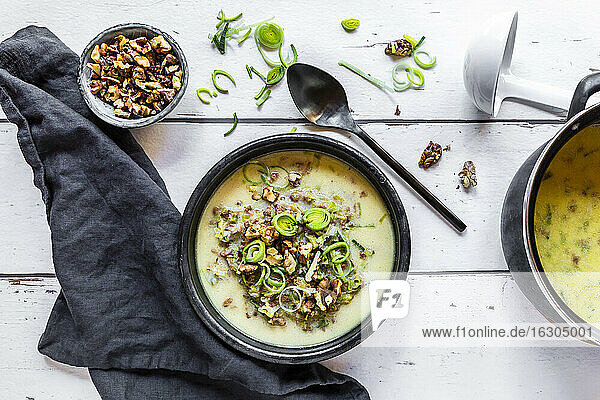 Bowl of vegetarian leek soup with cheese and roasted walnuts